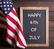 HAPPY 4th OF JULY Sign and the American Flag. American flag with HAPPY 4th OF JULY written on a chalkboard on a rustic wooden background stock photo