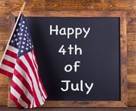 Happy 4th of July Sign. `Happy 4th of July` text on a chalkboard next to the American flag on a rustic wooden background royalty free stock photography