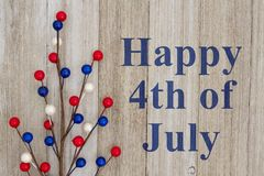 Happy 4th of July greeting. Happy 4th of July text with red, white and blue floral berry spray on weathered wood stock image