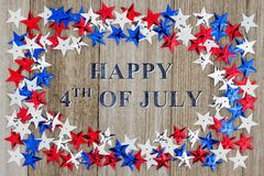 Happy 4th of July message. Happy 4th of July text with red, white and blue stars on weather wood stock photography
