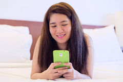 Happy Thai woman is playing and chatting on her mobile phone Stock Photo