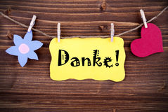 Happy Thank You Tag. Happy looking german Danke, which means Thank You, on a Yellow Label with a Flower and a Heart Hanging on a Line on Wood stock photo