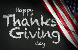 Happy Thanks Giving Day written on blackboard and the USA flag Royalty Free Stock Image
