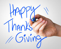 Happy Thanks Giving hand writing with a blue mark on a transparent board.  royalty free stock image