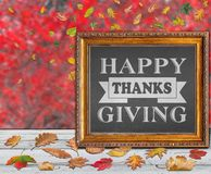Happy Thanks Giving inside frame with red and colored autumn leaves. In background Stock Photos
