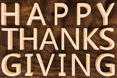 Happy Thanks Giving. The words happy thanks giving are formed out of wooden letters set agains a wooden background Royalty Free Stock Images