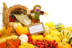 Happy Thanksgiving. Card and scarecrow among a cornucopia of autumn vegetables Royalty Free Stock Photography
