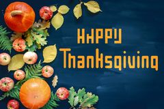 Happy Thanksgiving text with pumpkins and leaves over dark wood background stock images