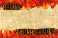 Happy Thanksgiving. Burlap background with wooden Happy Thanksgiving letterpress and autumn leaves Stock Photos