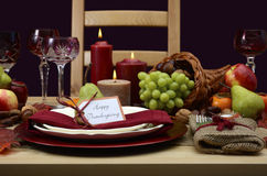 Happy Thanksgiving classic table setting. Happy Thanksgiving table setting in classic rustic colors on wood table with cornucopia centerpiece, candles and fruit Stock Photo