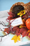 Happy Thanksgiving cornucopia - vertical. Happy Thanksgiving cornucopia with Autumn Fall leaves, pumpkin, sunflower and berries on white shabby chic tray against stock images