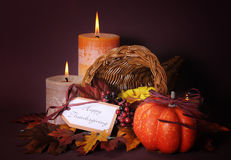 Happy Thanksgiving cornucopia wicker basket. With autumn leaves, pumpkin and greeting tag on candlelit background stock image