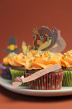 Happy Thanksgiving cupcakes with turkey, feast, and pilgrim hat topper decorations - closeup vertical. Stock Photos