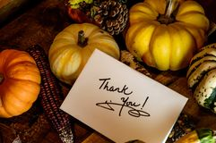 Happy Thanksgiving Day Card writing Thank you. Thank you card on beautiful autumn Thanksgiving day dinner table with traditional fall harvest decorations Royalty Free Stock Photography