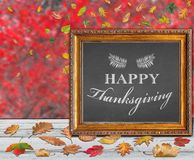 Happy Thanksgiving day design postcard with colored autumn leaves. On wooden terrace Stock Photos