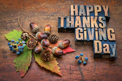 Happy Thanksgiving Day in wood type. Happy Thanksgiving Day - text in vintage letterpress wood type with fall decoration (acorns, cones, leaf and vine berries)