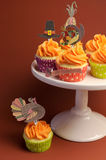 Happy Thanksgiving decorated cupcakes on pink stand with extra cupcake. Happy Thanksgiving decorated cupcakes with turkey, pilgrim hat and corn toppers on cake royalty free stock images