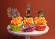 Happy Thanksgiving decorated cupcakes on pink stand. Happy Thanksgiving decorated cupcakes with turkey, pilgrim hat and corn toppers on cake stand against a stock photos