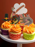 Happy Thanksgiving decorated cupcakes on pink stand vertical closeup. Happy Thanksgiving decorated cupcakes with turkey, pilgrim hat and corn toppers on cake stock photography