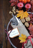 Happy Thanksgiving dining table place setting in traditional rustic country style. With hessian wrapped cutlery on rustic wood background royalty free stock photography