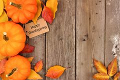 Happy Thanksgiving tag with side border of pumpkins and leaves over wood. Happy Thanksgiving gift tag with side border of pumpkins and autumn leaves over a Royalty Free Stock Photo
