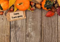 Happy Thanksgiving tag with autumn top border over wood Royalty Free Stock Photo