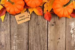 Happy Thanksgiving tag with top border of pumpkins and leaves over wood. Happy Thanksgiving gift tag with top border of pumpkins and autumn leaves over a rustic Royalty Free Stock Photo