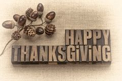Happy Thanksgiving greeting card in wood type. Happy Thanksgiving greeting card - word abstract in vintage letterpress wood type with acorns and cones fall royalty free stock images