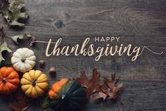 Happy Thanksgiving greeting text with pumpkins, squash and leaves over dark wood background. Happy Thanksgiving greeting script with colorful pumpkins, squash