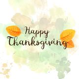 Happy Thanksgiving hand-drawn greeting text with autumn leaves. Stock Image