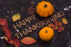 Happy Thanksgiving. Word with pumpkin and autumn leaves on black background royalty free stock images