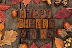 Happy Thanksgiving letterpress with frame of autumn leaves over wood Royalty Free Stock Photos
