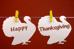 Happy Thanksgiving message greeting written across white turkeys hanging from pegs on a line. Celebrate Thanksgiving on the last Thursday in November with a royalty free stock photo