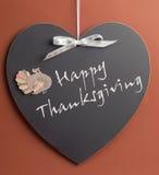 Happy Thanksgiving message written on heart shape blackboard. With turkey motif decoration stock photography