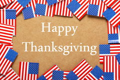 Happy Thanksgiving. The phrase Happy Thanksgiving in white text on a brown card background with a border of miniature flags of the United States of America stock photography