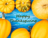 Happy thanksgiving on pumpkins frame on wooden sea blue background, flat lay. Halloween and thanksgiving concept. Happy thanksgiving text on blue wooden royalty free stock photo