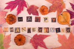 Happy Thanksgiving Sign. Happy Thanksgiving text with autumn leaves and objects on vintage surface royalty free stock images
