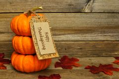 Happy Thanksgiving. Stack of mini pumpkins with Happy Thanksgiving tag on a wooden background Royalty Free Stock Photography