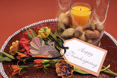 Happy Thanksgiving table setting centerpiece with ornage candle and nuts - aerial. Beautiful Happy Thanksgiving table setting centerpiece with ornage candle and Stock Photo