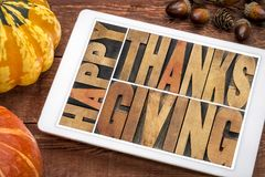 Happy Thanksgiving on tablet. Happy Thanksgiving greeting card - word abstract in vintage letterpress wood type blocks on a digital tablet with a winter squash stock images