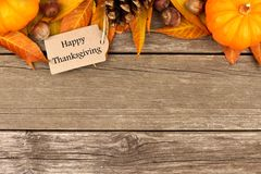 Happy Thanksgiving tag with autumn top border on rustic wood. Happy Thanksgiving tag with autumn top border of pumpkins, leaves and nuts on a rustic wooden Royalty Free Stock Photography