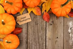 Happy Thanksgiving tag with corner border of pumpkins and leaves over wood. Happy Thanksgiving gift tag with corner border of pumpkins and autumn leaves over a Royalty Free Stock Image