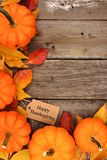 Happy Thanksgiving tag with corner border of pumpkins and leaves over wood. Happy Thanksgiving gift tag with corner border of pumpkins and autumn leaves over a Stock Photography