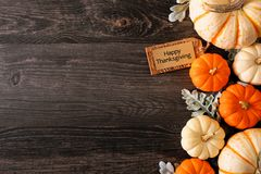 Happy Thanksgiving tag with fall side border of pumpkins and leaves on a dark wood background
