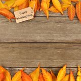 Happy Thanksgiving tag with frame of autumn leaves on wood Stock Photos