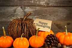 Happy Thanksgiving tag with pumpkins and autumn decor over wood Royalty Free Stock Photography