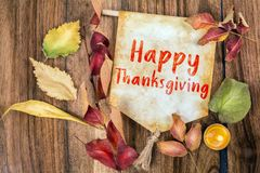 Happy thanksgiving text with autumn theme. Red yellow and green leaves with old paper and candle on walnut wood royalty free stock images
