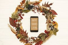 Happy Thanksgiving text on phone empty screen in autumn leaves w stock photography