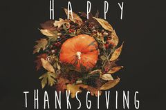 Happy Thanksgiving text on pumpkin in Fall leaves wreath with be royalty free stock photos
