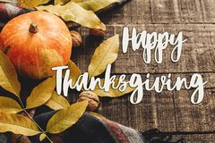 Happy thanksgiving text sign on autumn pumpkin with leaves and w Royalty Free Stock Image